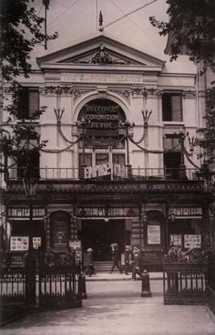 Photograph of a black and white postcard showing the façade of the Empire Theatre in Leicester Square, London. The image was taken in 1911.