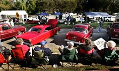 Folks line the sidewalks in their lawn chairs behind some of the classic cars at the Pig on a Ridge festival in Ridgeway, S.C. Barbecue cookers are in the background. The #festival is devoted to barbecue.