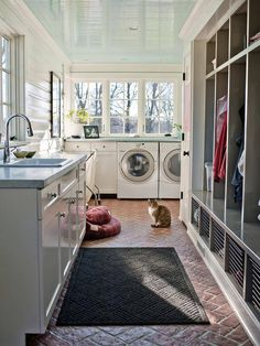 Laundry room to die for: huge room with natural light, hand-wash sink, drip-dry hanging space, and built-in storage...brick floor