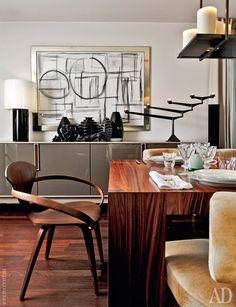 Зона столовой. Стол, Cassina. Желтые кресла по дизайну Вольфганга Йопа. Люстра по эскизам Кевина Рейли, фанерное кресло работы Нормана Чернера. На комоде, Cecchini, стоят вазы Venini, Arcade и Lalique. Картина авторства хозяина дома.
