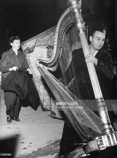 Fair of harp being carried into orchestra rehearsal.