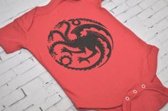Game of Thrones, House Targaryen Bodysuit/Creeper  Show your support for House Targaryen with this outfit. Design showing the House Targaryen dragon sigil. A wonderful baby shower gift for the book nerd, fantasy lovers!  Bodysuit is screen printed with eco friendly water based ink, and is made from 100% cotton.  A great gift for the Game of Thrones fan!  Care Instructions: Machine wash cold, tumble dry low.