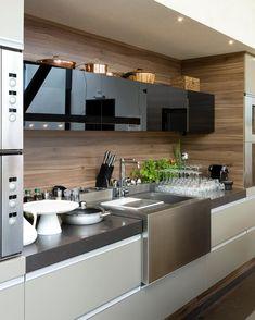 Cozinha super equipada com volume da cuba em inox destacado! A parede ao fundo com textura de madeira e as portas em vidro preto ficaram…
