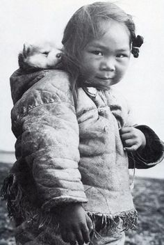 Little Inuit girl and her husky, 1920. Carrying the puppy in the same way her Mummy would've carried her. Adorable
