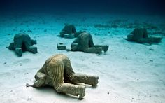 Sculptures of bankers with their heads in the sand have been dropped to the bottom of the ocean. The art work was created by Brit Jason deCaires-Taylor off the coast of Cancun, Mexico.
