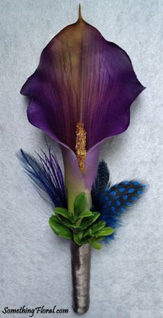 Realistic, artificial, purple calla lily boutonniere accented with a midnight blue pheasant feathers, green foliage, and a grey satin stem wrap. This was created for an Oregon couple's purple, midnight blue, and grey themed wedding.
