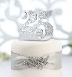 """Mark the occasion with this 25th anniversary cake pick. This cake pick, specially made for a 25th anniversary, measures 4"""" x 3.5"""" and is made of resin. The number 25 filled with floral grooves and spa"""