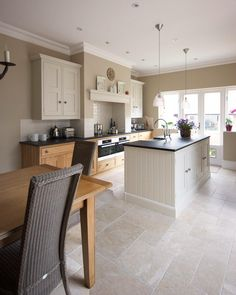 Opus patterned stone flooring adds to the high end look in this kitchen designed by Cheshire Furniture Company.