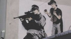 The image, featuring a police sniper about to be surprised by a boy bursting a paper bag, was painted over after black paint destroyed the image.