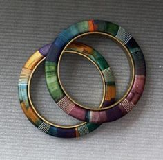 Lauren Abrams, brass channel bangles with polymer clay, painted with alcohol inks, and striped canes added.