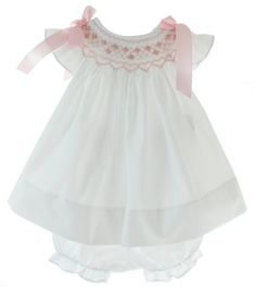 Infant girls white smocked angel bishop dress is smocked in pink with pink embroidered flowers and has pink satin bows on the shoulders. Baby girls beautiful white smocked dress comes with matching white bloomers. Girls Boutique, Boutique Clothing, Smocked Dresses For Girls, Punto Smok, Embroidered Clothes, Embroidered Flowers, Flower Embroidery, Smock Dress, Eyelet Dress