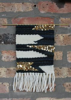Handwoven wall hanging on a hollow brass rod. Materials consist of hand spun wool in deep turquoise blue and off white, as well as gold sparkly...