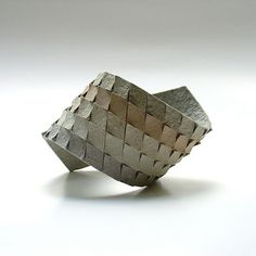https://flic.kr/p/4tERZU | Recycled Eggcrate Cardboard Bracelet by Israeli Jewelry Designer Dana Hakim Berkovich | This textural, modern bracelet cuff was made by Israeli jewelry designer Dana Hakim Berkovich by cutting diamond shapes into the cardboard. When rounding them into the bracelet shapes she generates a 3D effect - what I thought originally was a woven pattern. Berkovich's overall technique aims to recycle used materials into beautiful accessories and challenges users to rethink…