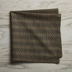 Black arrows herringbone this deep green chambray dinner napkin with menswear-inspired sophistication.