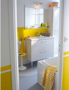 Dans une salle de bain blanche la couleur jaune c'est dynamique. Sur les murs blanc des bandes de peinture jaune suffisent à apporter du peps à une salle de bain monochrome.