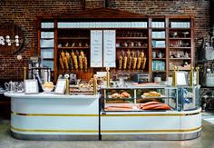 At Sadelle's in New York by Ken Fulk, a red-oak display showcasing bagels backs the to-go counter in French marble, brass, and enamel, all custom. Photography courtesy of ...
