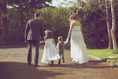 A bride, #groom, flower girl and page boy take a stroll in the sunshine. Photography: http://www.plusphotography.co.uk/