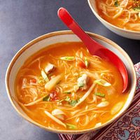Thai Chicken Noodle Soup    1 tablespoon sesame oil  4 cloves garlic, minced  2 teaspoons minced ginger  1 pound boneless, skinless chicken thighs, cut into 1-inch pieces  1/2 cup natural chunky peanut butter  1 cup crushed tomatoes  6 cups reduced-sodium chicken broth  1 tablespoon fish sauce  6 ounces rice noodles  2 cups shredded green cabbage  1 cup canned bean sprouts, drained  1/4 cup chopped scallions  Chopped cilantro (optional)  Chopped peanuts (optional)