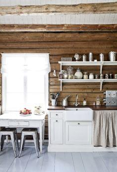 Vanhan hirsitalon uusi keittiö on tyylikkään kevyt. Yläkaappien sijaan seinällä on kauniit avohyllyt. Posliiniallas ja kaapinoven korvaava verho luovat menneen ajan tuntua.