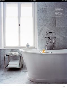 Oversize marble tiles. Luxe for less. Love the black handles on the faucets against the marble.