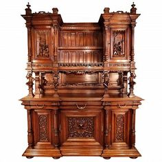 A sensationally and monumental carved late 19th Century French Henry II Walnut buffet with it's original hutch. The richly detailed carvings include jokers below wonderful scenes of men in a tavern. The bottom has three doors opening to a shelf inside, all below three drawers. Above are two doors on each side of a shelf, to display china. Finials finish the top.