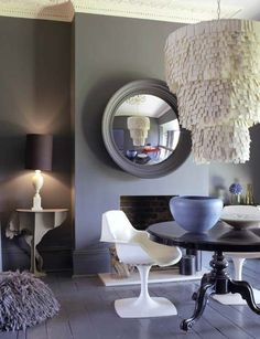Dining room. Abigail Ahern design. Dramatic chandelier and ostrich side table. Cool neutral color palette.