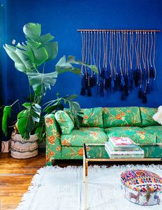 """After visiting Casa Azul in Mexico City — the cobalt blue home Frida Kahlo and Diego Rivera shared — Holley was inspired to hunt down a similar shade for her own eclectic living room. In the end, Benjamin Moore """"Blueberry Hill"""" fit the bill perfectly. Like the rest of her home, this spot is outfitted in secondhand finds."""