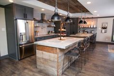 The expanded kitchen features twin islands with concrete countertops and bases wrapped in reclaimed wood.