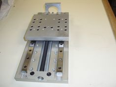 Arrangement of linear rails, lead screw bearing end support, and mounting plate with tapped holes.
