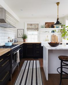 Rustic Soulful Kitchen | Ikea cabinets and butcher block, hand painted backsplash tile, waterfall island, open shelving