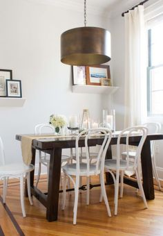 Thonet-style white chairs give the nook a more modern vibe and the contrasting color of the dark wood table makes the tiny space feel open and uncluttered.