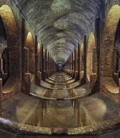 This is the long view down the brick arched rows of an underground reservoir beneath London. These cathedral-like subterranean cisterns were built in the 1800s to store rainwater for drinking. : Photo by @forgottenheritage. Read more about the abandoned underground tunnels and see more of his photos at the link in our bio!