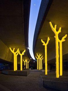 Muito interessante, não só a ideia de troncos servindo de sustentação, mas como eles se iluminam. A luz amarela bem forte é ótima para chamar a atenção e dar um destaque maior à estrutura.