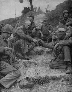 Ernie Pyle, war correspondent,  having a smoke with Marines of the First Marine Division on Okinawa