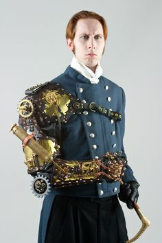 G. D. Falksen in steampunk attire including a mechanical arm wearable sculpture by Thomas Willeford utilizing a complex clockwork series of gears.