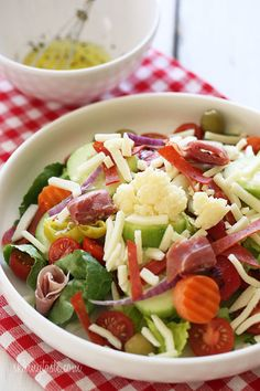 Italian Antipasto Salad - Chopped romaine hearts, shredded mozzarella, olives, prosciutto, turkey pepperoni, roasted red peppers, cucumbers, tomatoes, pepperoncini and Giardiniera (colorful vegetables in vinegar) – this quick Italian salad requires no cooking!