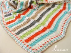Ana BC of Lanas de Ana has chosen such fun colours for this blanket (meant for a baby boy, but could actually be for a girl too). Just love them and the bold stripes she made. She uses dc stitches (two rows of each I believe) separated by two rows of white. She uses a mosaic stitch for the border.