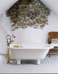 The rough-hewn wall of this 1825 house was left exposed, to reference the home's history. Placing a vintage footed tub in front of the wall makes it a focal point.