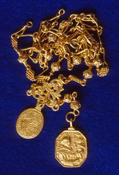 Caption 24- Gold religious medallions on a gold Rosary chain. Note that the medallion on the right is St. Christopher carrying the baby Jesus. -1715 Fleet