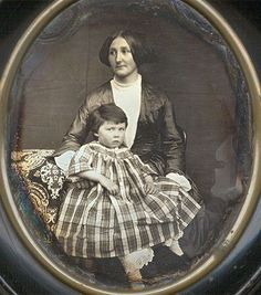 """French quarter plate daguerreotype of mother holding child, housed behind curved glass in the original black oval wood frame, with date of """"18 Octobre 1851"""" on the backing paper:"""