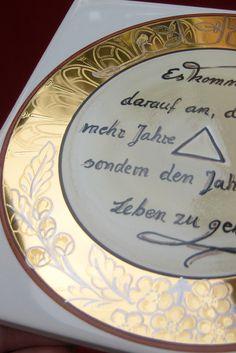 """Echtgold Malerei Einige Linien sind nach dem Goldbrand mit Platin verziert worden. In der Mitte ein Spruch, der auch beliebig vränderbar ist. Hier lautet der Spruch: """"Es kommt nicht darauf an, dem Leben mehr Jahre zu geben, sondern den Jahren mehr Leben zu geben."""""""