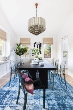 Dining room with a large blue rug, a black dining room table, acyclic dining room chairs, and a glass chandelier Ghost Chairs Dining, Black Dining Room Table, Dining Room Design, Dining Room Chairs, Dining Rooms, Dark Table, Dining Decor, Dining Area, Home Depot Shopping