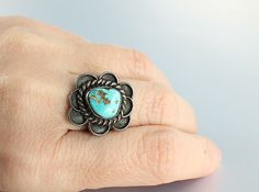 A very well made Navajo sterling silver ring featuring a beautiful natural turquoise stone in a floral setting. It is marked Jameson Lee on the inside