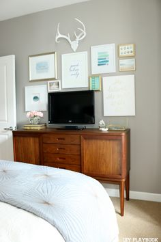 Hide your bedroom TV amongst a gallery wall of art. Find great art, canvases, and frames at HomeGoods to complete the look (Sponsored Pin)