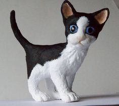Susie, a handmade paper clay papier mache sculpture of a black and white kitten