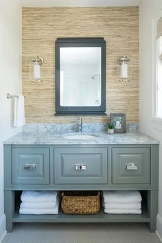 An extra wide gray washstand painted in Sherwin Williams Tin Lizzie features polished nickel pulls and an exposed lower shelf lined with towels and a woven storage basket.