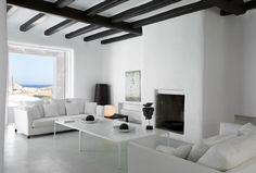 The interior is marked by the omnipresent white - on floors and walls - interrupted only by the wooden ceiling beams. #Greece #island #living_room