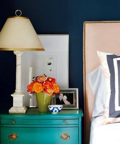 I love the navy walls paired with a soft turquoise bedside table and crisp sheets. The apricot bed head and orange flowers really add dimension too.