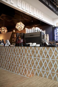 Tiny Geometrics - bar made from sheets of wood, and then painted with a white geometric print. the lights over the bar and work area echo this geometric pattern. support beam painted white to make the space feel lighter.