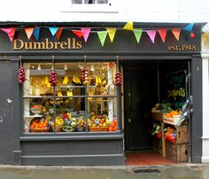 Another dark shop front with simple writing and bright, colourful bunting. Childrens Bookstore, Canterbury England, Sidewalk Cafe, Riomaggiore, Kent England, Cafe Shop, Shop Fronts, Lovely Shop, Wine Recipes